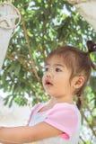 亚裔孩子是捅一` s头对看,她是非常逗人喜爱的 库存照片