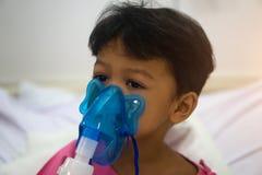 亚裔孩子男孩3岁有病残在雾化器面具 库存图片