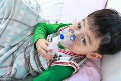 亚裔孩子顶视图拿着治疗的一台面具蒸气吸入器 免版税库存照片