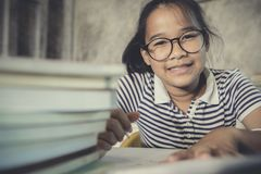 亚裔完成在家与堆一起使用的少年佩带的眼睛玻璃  免版税图库摄影