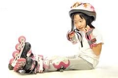 亚裔小女孩佩带直排轮式溜冰鞋和保护 免版税库存照片