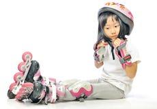 亚裔小女孩佩带直排轮式溜冰鞋和保护 库存照片