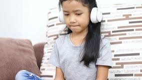 亚裔小女孩听到音乐由白色无线耳机技术流动应用概念 影视素材