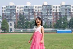 亚裔小女孩在草突出 免版税库存照片