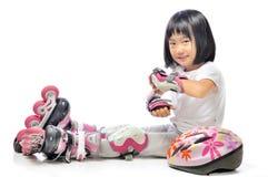亚裔小女孩在w佩带直排轮式溜冰鞋并且保护 图库摄影