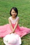 亚裔小女孩坐草 免版税图库摄影