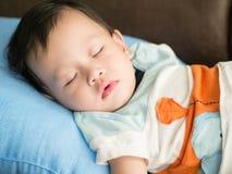 亚裔小孩落入在床上的微睡 免版税库存照片