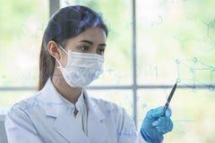 亚裔少女女学生科学家有文字和研究在实验室 库存照片
