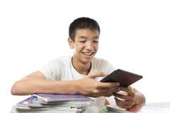 亚裔少年使用他的片剂的和愉快发现someth 免版税库存图片