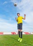 亚裔少年男孩在橄榄球场内,实践 跳跃和 库存照片