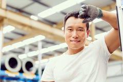 亚裔工作者在工厂地板上的生产设备 免版税库存照片