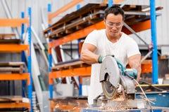 亚裔工作者在工厂地板上的生产设备 免版税库存图片