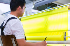 亚裔工作者在纺织品工厂控制织品 库存照片