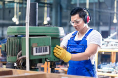 亚裔工作者在钻床的工厂 库存照片