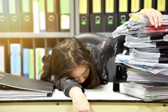亚裔工作者妇女睡觉在工作场所的,疲乏的妇女睡着从努力工作,大量工作, 免版税库存图片