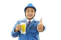 亚裔工作者饮用的啤酒 免版税库存照片