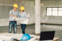 年轻亚裔工程师在建造场所结合工作在大厦图纸 土木工程,工业或者家庭整修 图库摄影