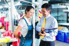 亚裔工头在给训练的纺织品工厂 免版税库存图片