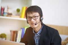 亚裔帅哥操作员在工作,企业广告通信c 免版税库存照片