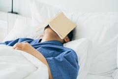 亚裔帅哥读了书,当睡觉时 人书套睡意导致睡眠 充分睡眠的概念 好休眠 库存图片
