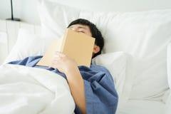 亚裔帅哥读了书,当睡觉时 人书套睡意导致睡眠 充分睡眠的概念 好休眠 免版税库存照片