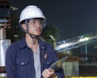 亚裔年轻人检查在工业工厂里面的机器 图库摄影