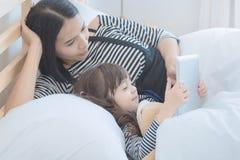 亚裔年轻在巧妙的片剂的母亲观看的动画片有她的女儿的 库存照片