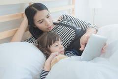 亚裔年轻在巧妙的片剂的母亲观看的动画片有她的女儿的 库存图片