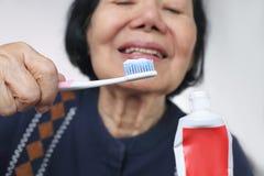 亚裔年长妇女尝试的用途牙刷 牙齿 免版税库存照片