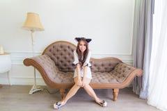 年轻亚裔微笑妇女坐一个长沙发在现代屋子里 免版税库存照片