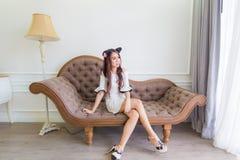 年轻亚裔微笑妇女坐一个长沙发在现代屋子里 免版税库存图片