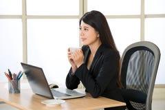亚裔微笑的女商人享受在膝上型计算机的咖啡休息 免版税图库摄影