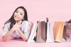 亚裔微笑的妇女很满意对她的在便衣的购物有在墙壁桃红色背景,葡萄酒口气的购物袋的 库存图片