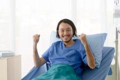 亚裔患者坐与举胳膊的医院病床 免版税库存图片