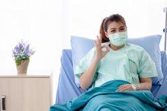 亚裔患者坐医院病床,少女手势好标志 免版税库存图片