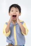 亚裔愉快的男孩画象激发面孔和看照相机 免版税库存图片