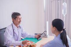 亚裔成熟男性医生 微笑,给咨询的医生解释医疗给患者 免版税库存图片