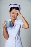 年轻亚裔护士得到了与一杯咖啡的头疼 免版税库存照片