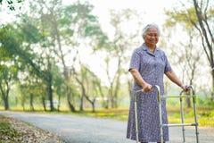 亚裔护士生理治疗师医生在医院关心,帮助和支持资深或年长与步行者的老妇人妇女耐心步行 库存图片