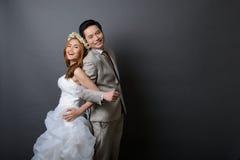 年轻亚裔摆在和微笑在前的演播室的新郎和新娘 免版税库存图片