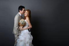 年轻亚裔摆在和微笑在前的演播室的新郎和新娘 库存照片