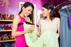 亚裔时尚商店销售夫人提供的礼服 免版税库存图片