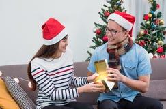 亚裔有女朋友的人开放金礼物盒在圣诞派对,假日庆祝的沙发的 概念查出的惊奇白色 库存照片