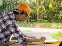 亚裔木匠业工程师计划一个工作修建大厦 免版税库存图片