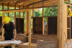亚裔木匠业工程师计划一个工作修建大厦 免版税图库摄影