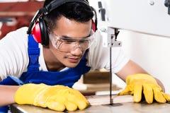 亚裔木匠或工作者看见了与木头 免版税库存照片