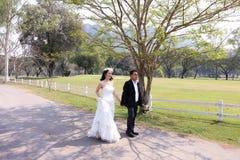 亚裔步行沿着向下庭院的新娘和她的新郎在阳光下 图库摄影