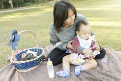 亚裔母亲举行婴孩,当家庭野餐在公园 库存照片
