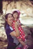 亚裔母亲和可爱的女儿在假日 减速火箭的样式 免版税库存图片