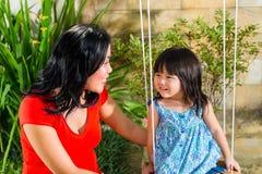 亚裔母亲和女儿在家在庭院里 免版税库存照片
